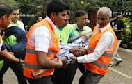 Volunteers at the MP Shah hospital assist a man whose relative was killed in Saturday's attack at the Westgate shopping mall in Nairobi September 22, 2013. REUTERS/Thomas Mukoya