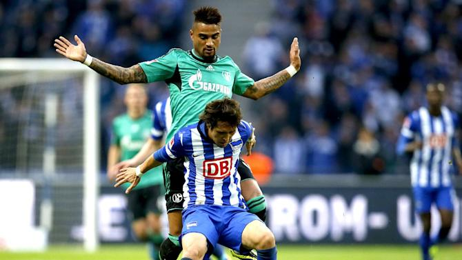 Schalke's Kevin-Prince Boateng of Ghana, rear, and Berlin's Hajime Hosogai of Japan, front, challenge for the ball during the German first division Bundesliga soccer match between Hertha BSC and FC Schalke 04 in Berlin, Germany, Saturday, Nov. 2, 2013
