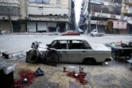 Blood stains on the pavement after artillery mortar shells landed opposite a bread shop operated by the civilian arm of the Free Syrian Army in the Bustan Al-Qasr neighborhood of Aleppo on Monday.