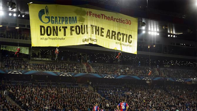 """FILE- In this Tuesday, Oct. 1, 2013, Greenpeace activists display a banner calling for protection of the Arctic region, during a Champions League group E group stage soccer match between Switzerland's FC Basel and Germany's FC Schalke 04 at the St. Jakob-Park stadium in Basel, Switzerland. Swiss club Basel says Thursday, Nov. 14, 2013, Greenpeace has donated money to a charity supported by the club after activists disrupted the Champions League match to make an environmental protest. Basel says Greenpeace gave """"a considerable sum"""" to a children's home in Romania following the Oct. 1 incident"""