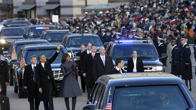 President Barck Obama and first lady Michelle Obama walk in the Inaugural Parade after the ceremonial swearing-in for the 57th Presidential Inauguration on Capitol Hill in Washington, Monday, Jan. 21, 2013. (AP Photo/Susan Walsh)