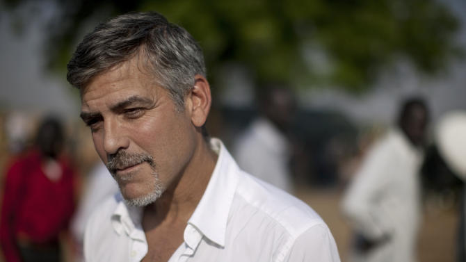 FILE - In this Jan. 9, 2011 file photo, George Clooney stands outside a polling station on the first day of voting  in Juba, then capital of southern Sudan. Actor and human rights activist George Clooney made a quiet visit to a volatile border region between Sudan and South Sudan last week, ahead of testimony he's giving before a U.S. Senate committee on Wednesday, March 14, 2012. (AP Photo/Pete Muller, File)