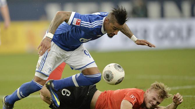 Schalke's Kevin-Prince Boateng of Ghana, left, and Mainz's Johannes Geis challenge for the ball during the German Bundesliga soccer match between FC Schalke 04 and FSV Mainz 05 in Gelsenkirchen,  Germany, Friday, Feb. 21, 2014