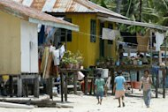 Children of illegal Filipino immigrants are pictured on April 13, 2008 walking past residences in Sabah. One former official said some 100,000 identity cards were handed out to Filipinos and Indonesians in Sabah in 1993 ahead of a crucial state election, Malaysian news reports said