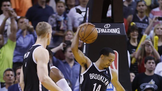 Brooklyn Nets guard Shaun Livingston (14) celebrates at the buzzer as the Nets defeated the Miami Heat 96-95 in an NBA basketball game, Wednesday, March 12, 2014, in Miami