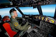 A handout photo taken on March 19, 2014 shows Royal Australian Air Force pilot Flight Lieutenant Russell Adams from 10 Squadron, flying his AP-3C Orion over the Southern Indian Ocean during the search for missing Malaysian Airlines flight MH370