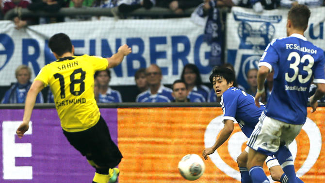 Dortmund's Nuri Sahin of Turkey, left, scores  during the German first division Bundesliga soccer match between Schalke 04 and BvB Borussia Dortmund  in Gelsenkirchen, Germany, Saturday, Oct. 26, 2013