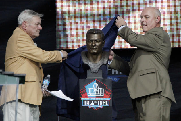 Former NFL player Jack Butler, left, and his presenter, son John Butler, unveil his bust during an induction ceremony at the Pro Football Hall of Fame, Saturday, Aug. 4, 2012, in Canton, Ohio. (AP Pho
