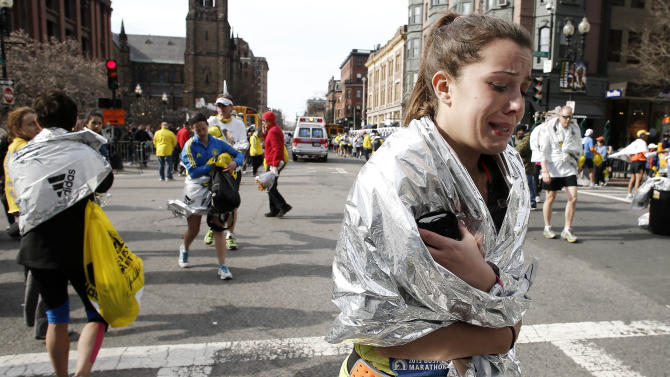A Boston Marathon runner leaves the course crying near Copley Square following an explosion at the finish line in Boston on Monday, April 15, 2013. (AP Photo/Winslow Townson)
