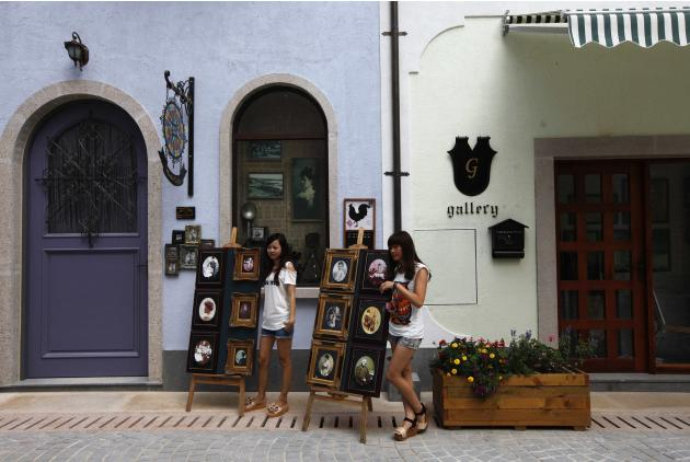 Women pose for pictures at the replica of Austria's UNESCO heritage site, Hallstatt village, in Huizhou