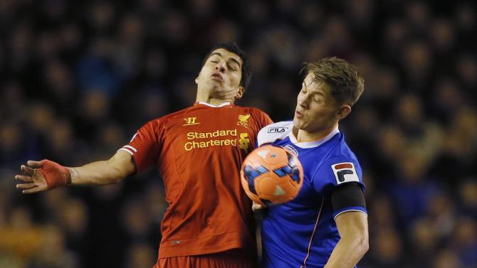Liverpool's Suarez challenges Oldham Athletic's Tarkowski during their FA Cup third round soccer match at Anfield in Liverpool