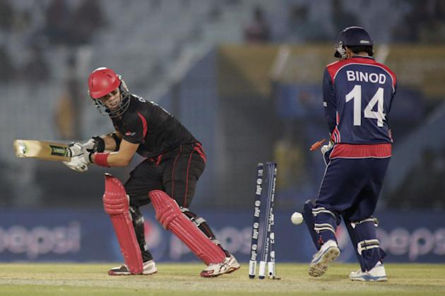 Hong Kong's Mark Chapman, left, is bowled out during their ICC Twenty20 Cricket World Cup match against Nepal in Chittagong, Bangladesh, Sunday, March 16, 2014. (AP Photo/Bikas Das)