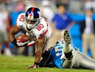 Victor Cruz of the New York Giants dives over James Anderson of the Carolina Panthers for extra yardage during play on September 20, 2012 in Charlotte, North Carolina. The Giants won 36-7