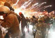 Fireworks explode near anti-government protester during clashes with riot police at the Independence Square in Kiev February 18, 2014. REUTERS/Vasily Fedosenko