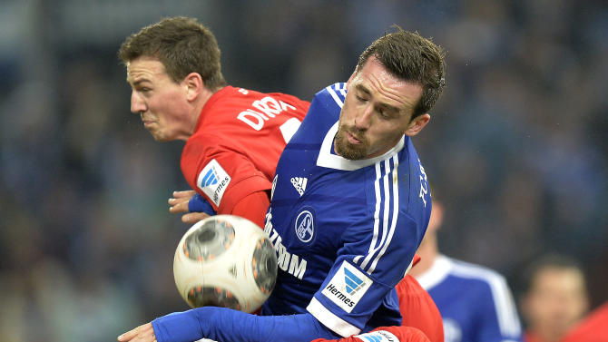 Schalke's Christian Fuchs jumps for the ball between Freiburg's defense during the German Bundesliga soccer match between FC Schalke 04 and SC Freiburg in Gelsenkirchen, Germany, Sunday, Dec. 15, 2013