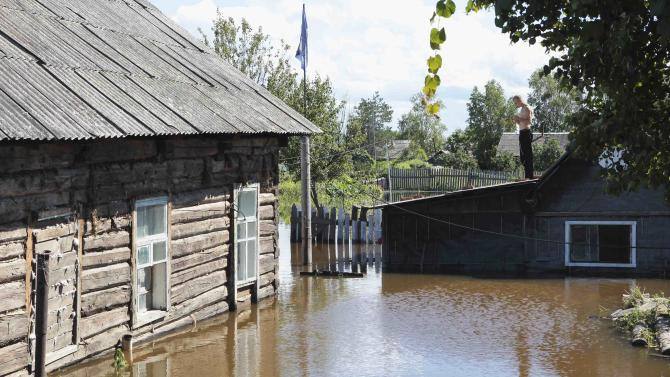 A local resident stands on the roof of a building in the flooded settlement of Krasnaya Rechka