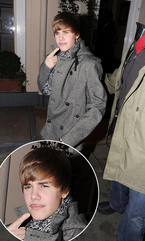 """Baby"" singer Justin Bieber sports a drawn-on moustache and torments his bodyguard with a toy helicopter as he leaves one of London's most exclusive restaurants"