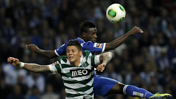 FC Porto's Silvestre Varela, back, goes for a high ball Sporting's Marcos Rojo, from Argentina, in a Portuguese League soccer match at the Dragao stadium in Porto, Portugal, Sunday, Oct. 27, 2013. Porto won 3-1 and stands top of the league