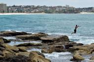 A man jumps into the sea to cool off at Manly beach in Sydney on January 8, 2013