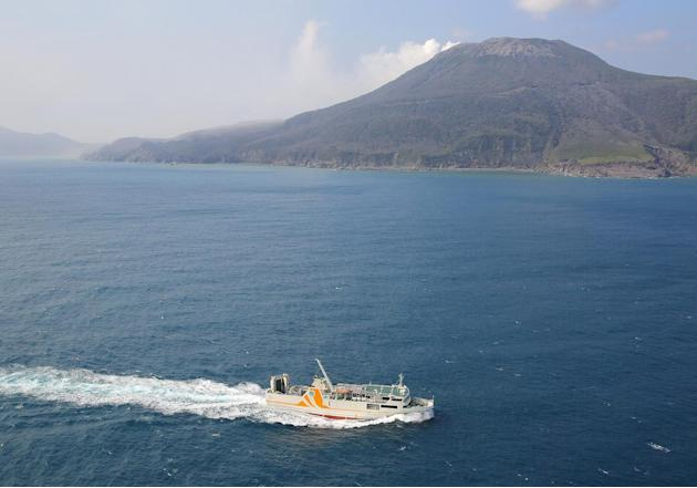 A ferry carries evacuees from Kuchinoerabu island, background, southern Japan, Friday, May 29, 2015. Mount Shindake erupted in spectacular fashion on the small island on Friday, spewing out rocks and