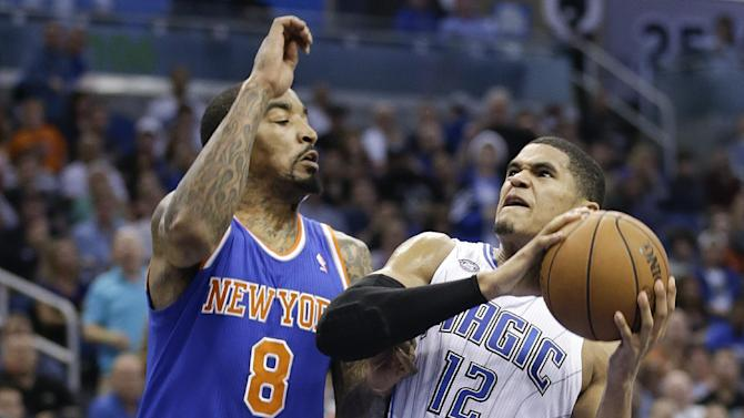 Orlando Magic's Tobias Harris (12) attempts to shoot while trying to get around New York Knicks' J.R. Smith (8) in the second half of an NBA basketball game in Orlando, Fla., Monday, Dec. 23, 2013. New York won the game 103-98
