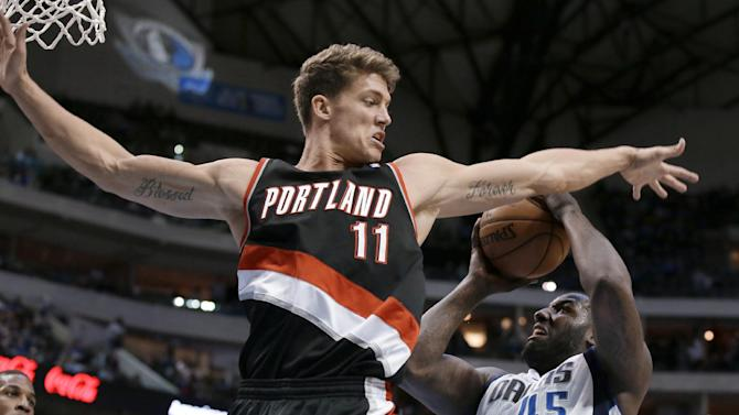 Portland Trail Blazers center Meyers Leonard (11) denies Dallas Mavericks' DeJuan Blair (45) a shot attempt during the second half of an NBA basketball game, Saturday, Jan. 18, 2014, in Dallas. The Trail Blazers won 127-111
