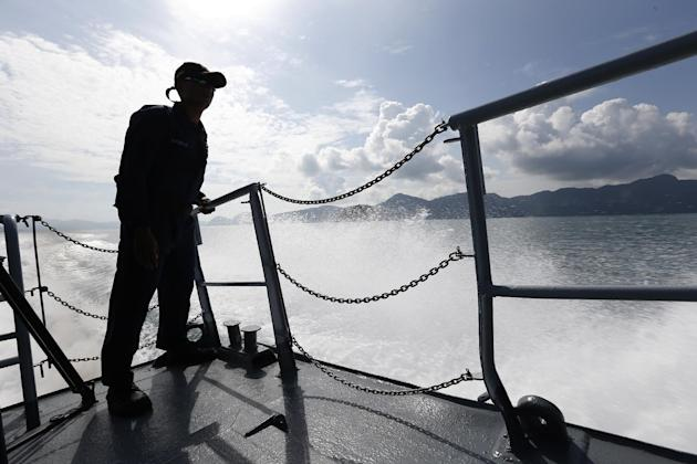 A member of Malaysian Navy is silhouetted as he stands guard on the bow of a corvette ship during a media trip for the search and rescue mission of Rohingya migrants in Langkawi, Malaysia on Thursday,