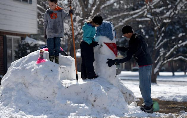 Jerry Vicker, left, and Savannah Sucic, middle, build a snowman with the help of Chris Sucic, Thursday, Feb. 26, 2015, in Huntsville, Ala. A record winter storm that dumped a foot of snow on north Ala