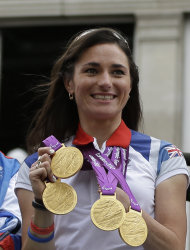 Britain's cyclist Sarah Storey holds her gold medals as the Team GB Olympic and Paralympic teams parade in the streets of London, Monday, Sept. 10, 2012. Our Greatest Team Parade, the procession of athletes, celebrates the achievements of British Olympians and Paralympians at the London 2012 Games. (AP Photo/Lefteris Pitarakis)