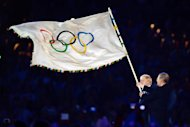 The Olympic flag is handed from London Mayor, Boris Johnson, left, to the International Olympic Committee President Jacques Rogge, during the Closing Ceremony of the 2012 Summer Olympics on Sunday, Aug. 12, 2012, in London. (AP Photo/Jeff J Mitchell, Pool)