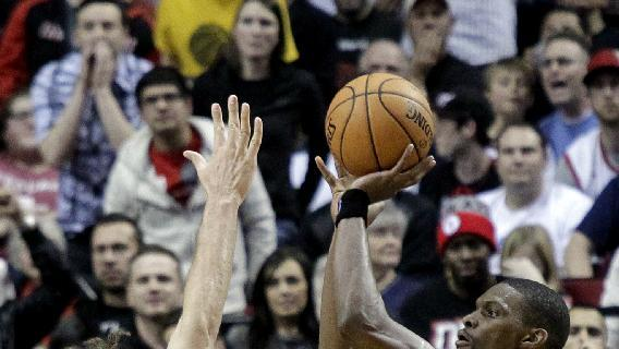 Miami Heat center Chris Bosh, right, shoots over Portland Trail Blazers center Robin Lopez during an NBA basketball game in Portland, Ore., Saturday, Dec. 28, 2013. Bosh led the Heat in scoring with 37 points and sank a three point shot with less than a second to go to beat the Trail Blazers 108-107