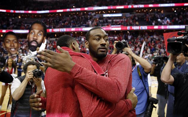Washington Wizards guard Bradley Beal, left, and John Wall embrace after Game 4 of the first round of the NBA basketball playoffs against the Toronto Raptors, Sunday, April 26, 2015, in Washington. Th