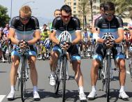 """From left Germany's Fabian Wegmann, Portugal's Bruno Pires and Austria's Thomas Rohregger, cyclists of the Leopard-Trek team observe a minute of silence for their teammate Wouter Weylandt prior to the start the fourth stage of the Giro d'Italia, Tour of Italy cycling race, in Genoa, Italy, Tuesday, May 10, 2011. The Leopard-Trek team will continue to ride in the Giro d'Italia despite the death of cyclist Wouter Weylandt. The 26-year-old Belgian crashed Monday during a descent after clipping a wall during the third stage of the race and died at the scene despite medical staff trying to revive him for 40 minutes. """"We will start out of respect for the family of Weylandt and also to share our grief with the world of cycling,"""" Leopard Trek general manager Brian Nygaard said Tuesday."""