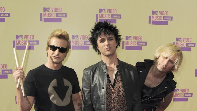 FILE - In this Sept. 6, 2012 file photo, members of Green Day, from left, Tre Cool, Billie Joe Armstrong and Mike Dirnt attend the MTV Video Music Awards, in Los Angeles. The Grammy-winning punk band announced new tour dates, Monday, Dec. 31, 2012. Green Day's tour is scheduled to begin in March 28, 2013 in Chicago. (Photo by Jordan Strauss/Invision/AP, File)