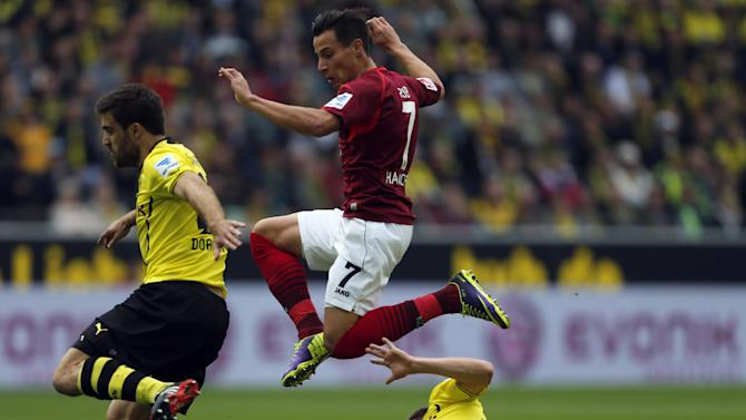 Hannover's Edgar Prib, center, jumps over Dortmund's Erik Durm as he challenges with Dortmund's Sokratis of Greece, left, for the ball during the German first division Bundesliga soccer match between BvB Borussia Dortmund and Hannover 96 in Dortmund, Germany, Saturday, Oct. 19, 2013
