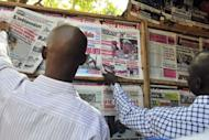 """Locals read newspapers in Bamako on the situation in the north. The UN Security Council called for an immediate ceasefire and return to democracy in Mali, prompting an announcement of an end to """"military operations"""" by Tuareg rebels in the north."""