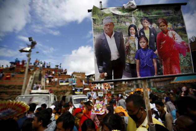 "A portrait of a family who died is carried by a family member during a parade to mark the Gaijatra festival, also known as ""cow festival,"" in Kathmandu"