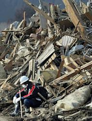 A fire fighter takes a rest before a pile of debris at Rikuzentakada city in Iwate prefecture. Japan raced to avert a meltdown of two reactors at a quake-hit nuclear plant Monday as the death toll from the disaster on the ravaged northeast coast was forecast to exceed 10,000
