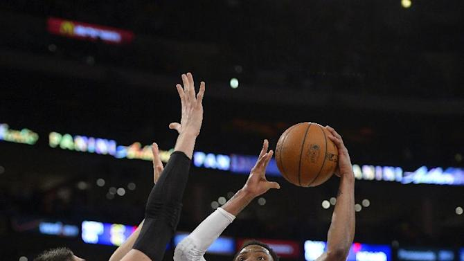 Los Angeles Lakers guard Kent Bazemore, center, goes up for a shot as Orlando Magic center Nikola Vucevic, left, and guard Ronnie Price defend during the first half of an NBA basketball game, Sunday, March 23, 2014, in Los Angeles