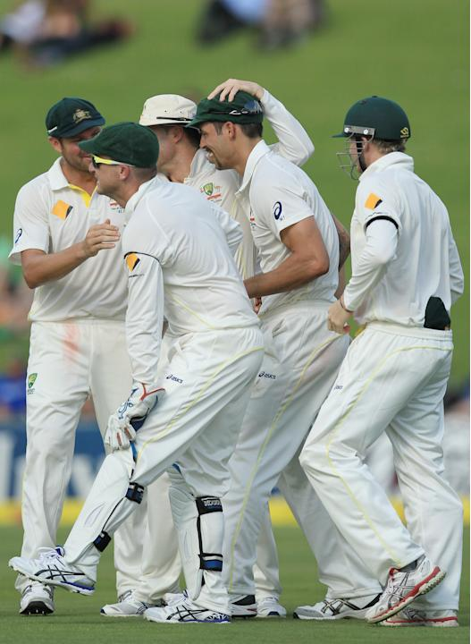 Australia's Mitchell Johnson, second from right, celebrates with teammates after taking a catch to dismissing South Africa's batsman JP Duminy, on the second day of their their cricket test ma