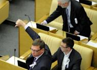 """Wearing white ribbons, a symbol of the Russian opposition, """"Just Russia"""" party members vote against a new bill that would steeply increase fines for illegal protest activity, in the State Duma lower house of parliament, in Moscow, May 22, 2012"""