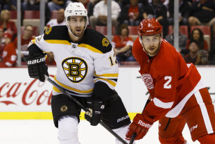 Oct 15, 2014; Detroit, MI, USA; Boston Bruins left wing Simon Gagne (12) defended by Detroit Red Wings defenseman Brendan Smith (2) in the second period at Joe Louis Arena. (Rick Osentoski-USA TODAY Sports)