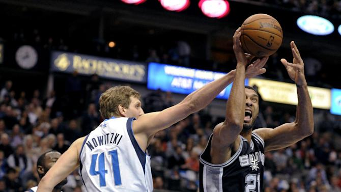 Dallas Mavericks forward Dirk Nowitzki (41) defends a shot by San Antonio Spurs forward Tim Duncan (21) during the first half of an NBA basketball game, Thursday, Dec. 26, 2013, in Dallas