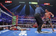 Referee Kenny Bayless (C) holds back Juan Manuel Marquez (R) as Manny Pacquiao lies face down on the mat after being knocked out by Marquez, on December 8, at the MGM Grand Garden in Las Vegas, Nevada