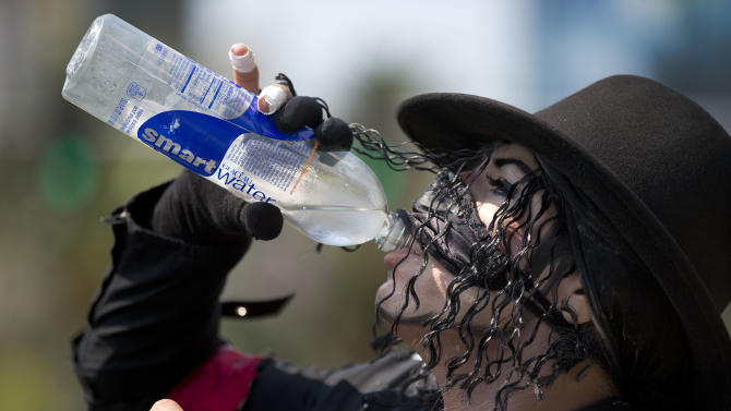 Michael Jackson impersonator Juan Carlos Gomez drinks some water as he takes a break from posing for photos with tourists along The Strip, Friday, June 28, 2013 in Las Vegas. A blazing heat wave expected to send the mercury soaring to nearly 120 degrees in Phoenix and Las Vegas settled over the West on Friday, threatening to ground airliners and raising fears that people and pets will get burned on the scalding pavement. (AP Photo/Julie Jacobson)