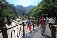 Tourists pose for photos at the Mount Kumgang international tourist zone in North Korea, August 31, 2011. North Korea has reopened a hotline with South Korea as the two sides agreed to weekend talks aimed at mending ties after months of soaring tensions and threats of nuclear war