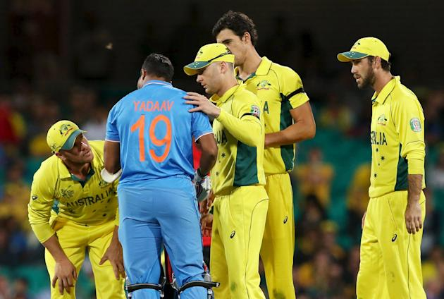 Australia's teammates look at India's batsmen Umesh Yadav's face after his helmet was struck by a delivery during their Cricket World Cup semi-final match in Sydney