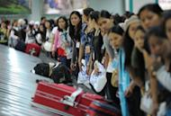 Philippine workers, who had been working in Syria, wait for their luggage after they disembarked from a plane chartered by the International Organization for Migration at the international airport in Manila. Over 260 Philippine workers returned from Syria, recounting tales of the violence that forced them to flee the country, even if it meant risking poverty at home