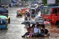 Bangladeshi pedestrians hitch a ride on a rickshaw van as they attempt to stay dry over flood waters in the capital Dhaka, in 2009. Asian countries dominate a league table of economies most at risk from earthquakes, floods, storms and other natural hazards, according to research published on Wednesday