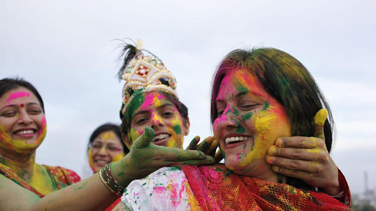 "Indian women smear colors on each others faces as they celebrate ""Holi"", the Indian festival of colors in Allahabad, India, Tuesday, March 26, 2013. Holi, the Hindu festival of color heralds the arrival of spring.(AP Photo/ Rajesh Kumar Singh)"